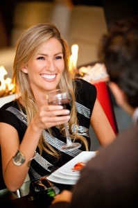 woman smiling with glass of wine